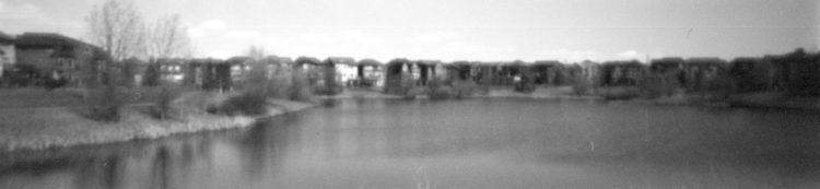 pinhole photo of houses by a pond