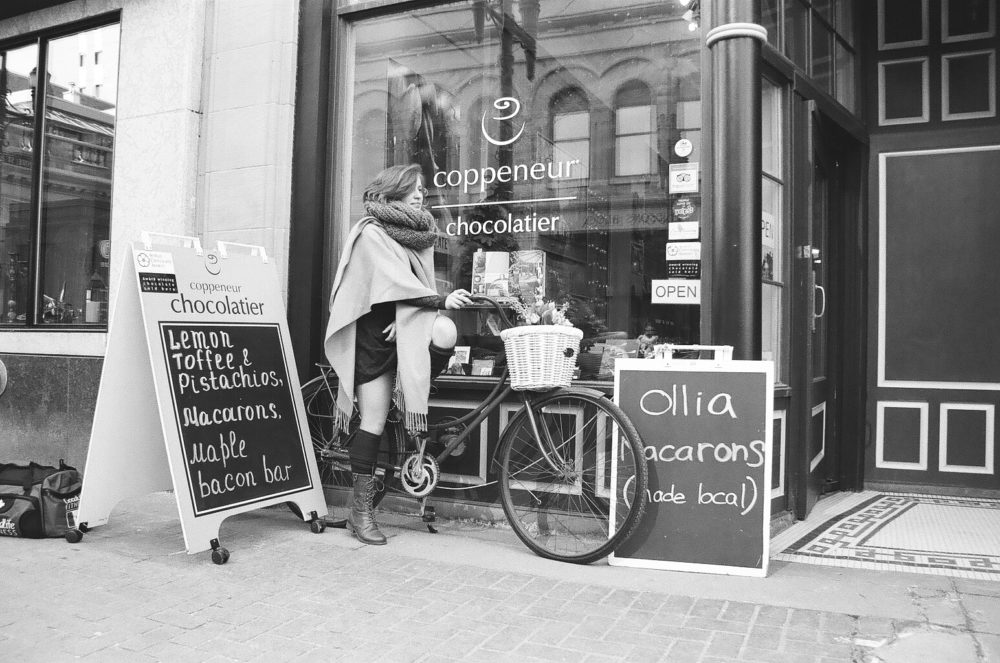 young woman on a bicycle at a chocolatier